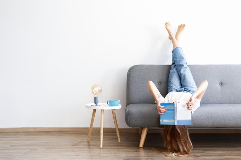 Una persona a testa in giù sul divano.