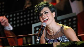 Dolcenera canta, seduta, al piano, di fronte al microfono, con dietro dei leggii