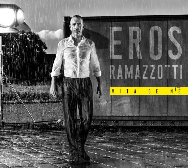 Eros Ramazzotti, in bianco e nero, in piedi, sotto la pioggia con la scritta Vita ce n'è