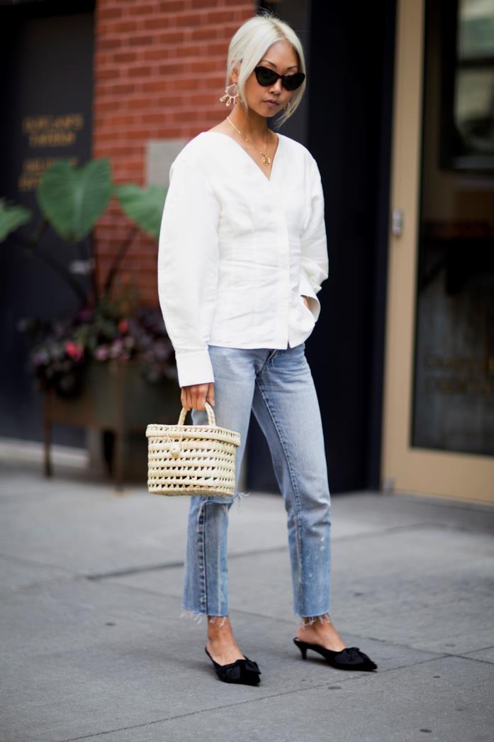 Secchiello in paglia indossato con camicia bianca e jeans
