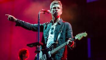 Noel Gallagher in piedi, con la chitarra in mano, di fronte a un microfono, con un braccio alzato