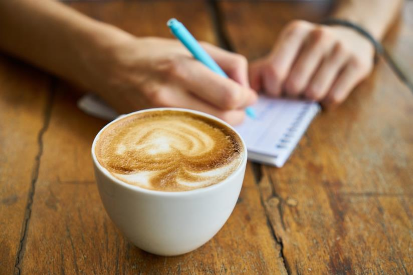 Tazza di cappuccino vicino a un ragazzo che scrive su un taccuino
