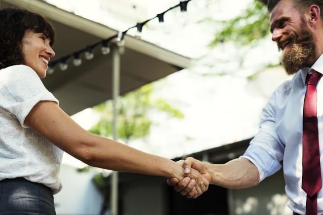 Un uomo e una donna che si stringono la mano.