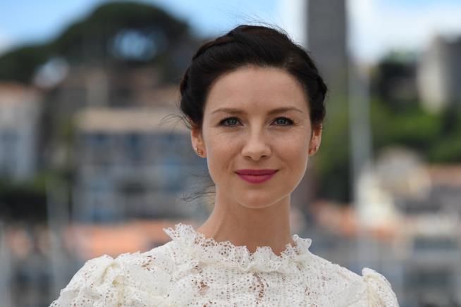 Caitriona Balfe in primo piano vestita di bianco