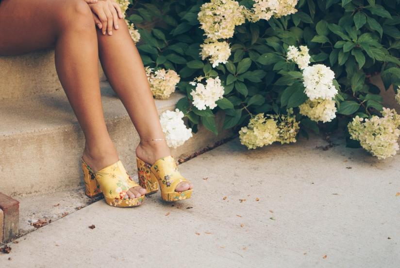 Donna con dolore al ginocchio e scarpe con tacco