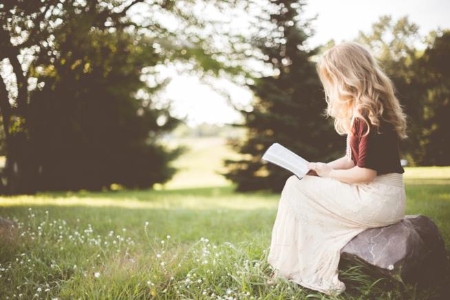 Donna seduta in un prato legge un libro