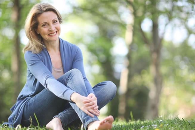 Una donna sorride seduta tra gli alberi