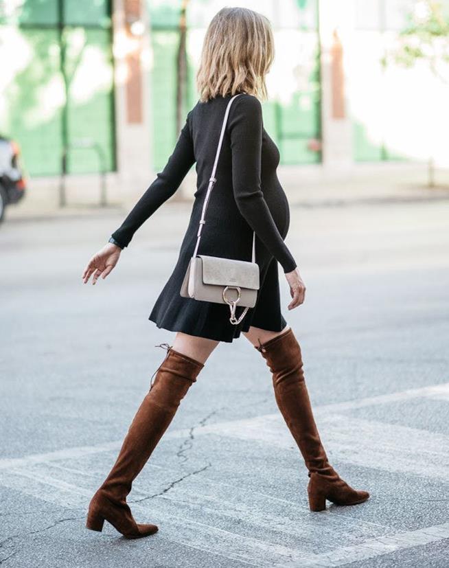 Vestito nero con stivali sopra al ginocchio