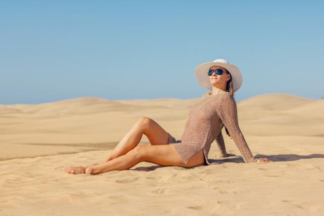 Ragazza prende il sole sulla sabbia