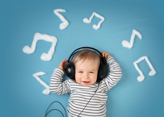 Un bambino ascolta divertito una canzone