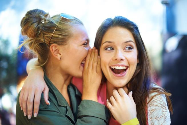 Una ragazza parla all'orecchio dell'amica