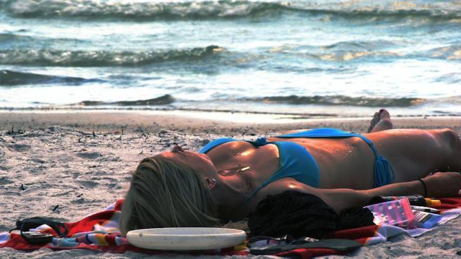 Donna che prende il sole in riva al mare.