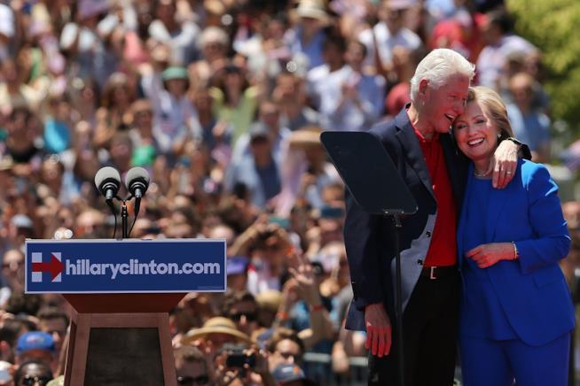 Hillary e Bill Clinton durante un evento ufficiale abbracciati su un palco