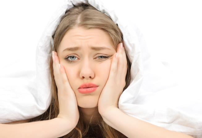 Primo piano di una donna sconsolata sotto le coperte