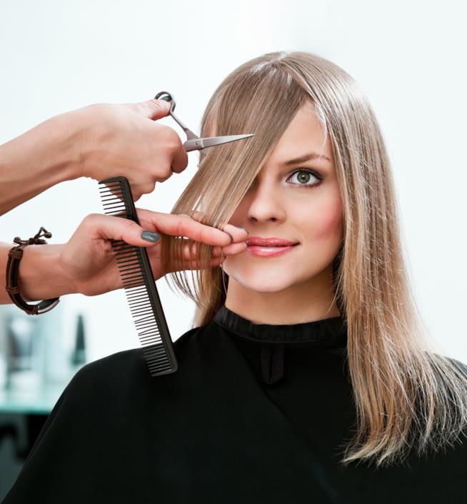 Dettaglio di mani che procedono al taglio dei capelli