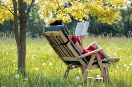 Ragazza che legge un libro seduta su una sdraio in giardino