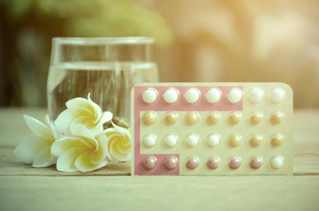 Confezione di pillole anticoncezionali vicino a un bicchiere di acqua