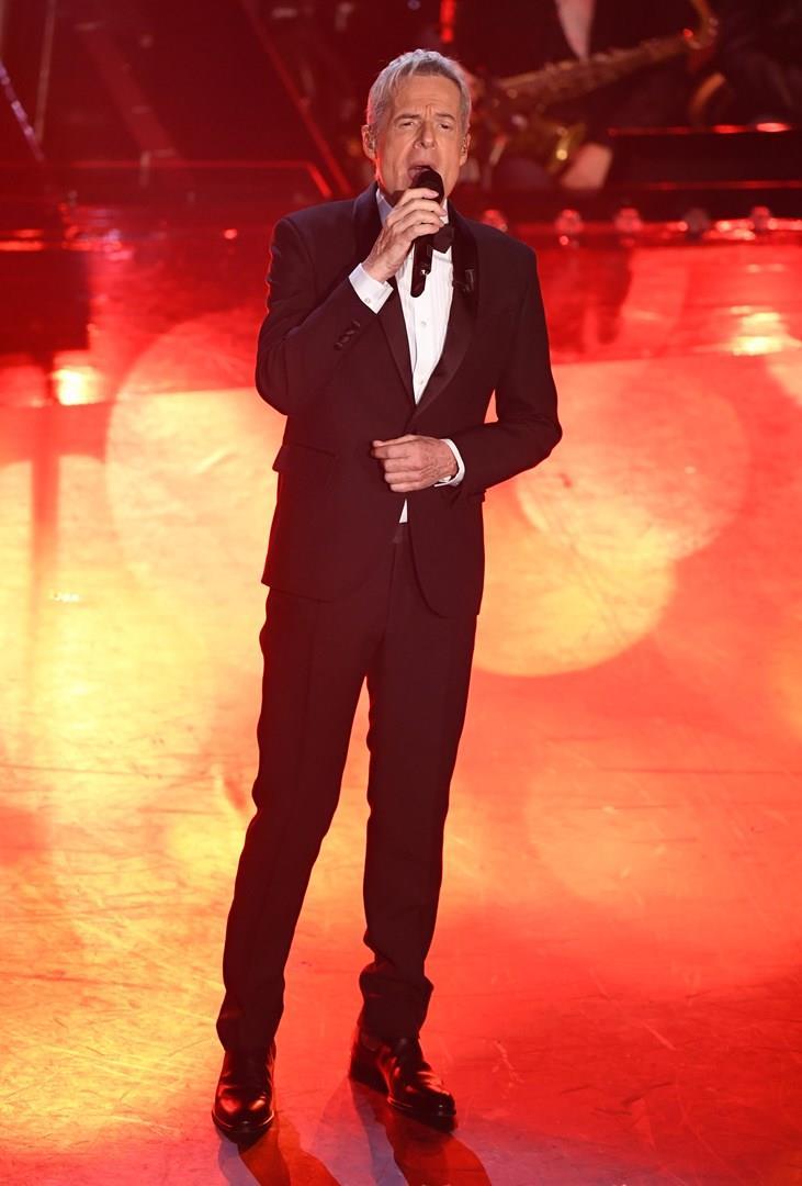 Claudio Baglioni, in piedi, in nero, canta al microfono, su sfondo rosso