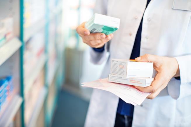 Farmacista con in mano confezioni di farmaci