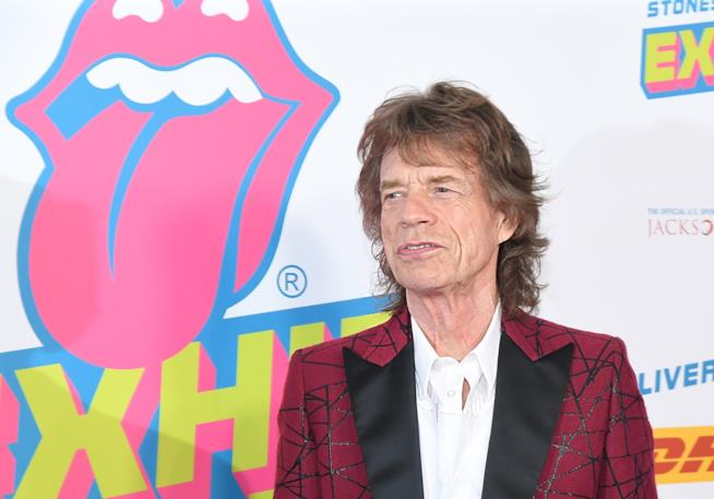 Mick Jagger davanti al logo dei suoi Rolling Stones