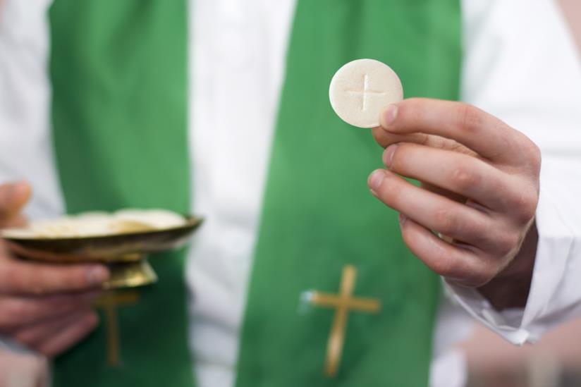 Prete con in mano l'eucaristia