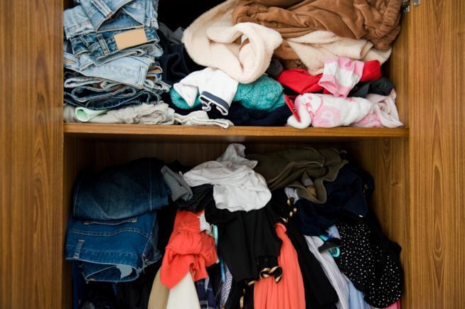 Tanti vestiti in disordine stipati in un armadio aperto