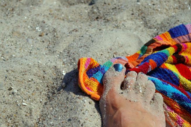 Un piede poggiato sopra ad un asciugamano.