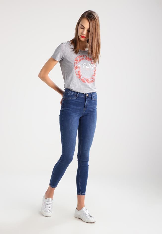 Ragazza indossa jeans skinny e maglia grigia