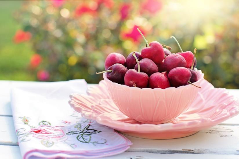 Tazza da tè piena di ciliege su un tavolino