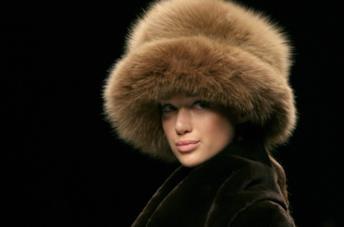 una modella sfila indossando un abito ed un copricapo in pelliccia