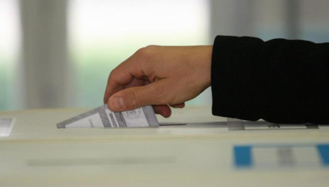 Una persona consegna la sua scheda elettorale