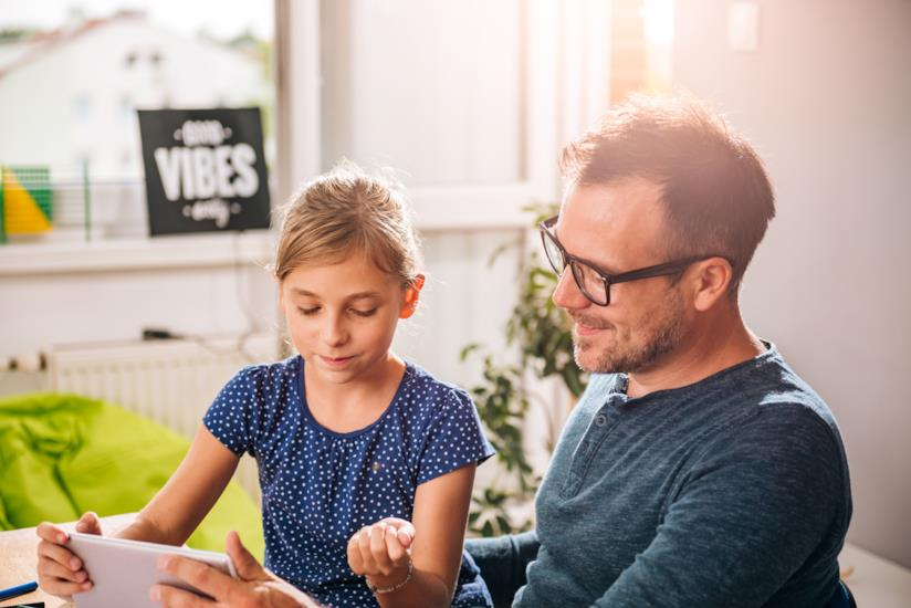 Padre e figlia usano tablet e social insieme