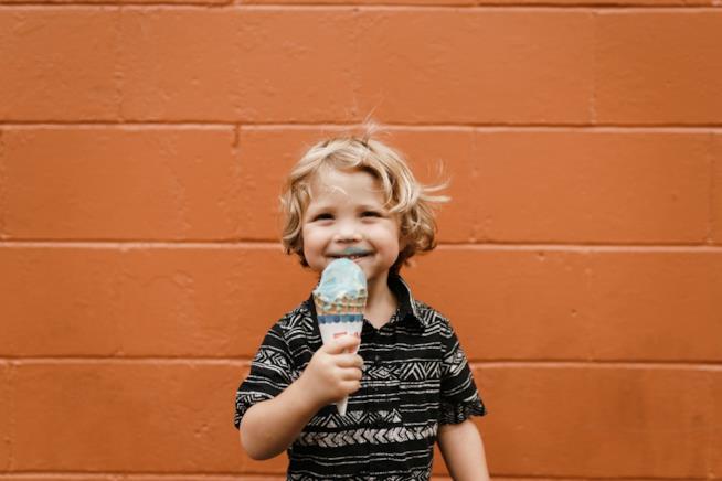 Bambino che mangia da solo un gelato