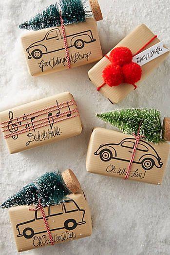Pacchetti di Natale con mini abiti fissati in cima
