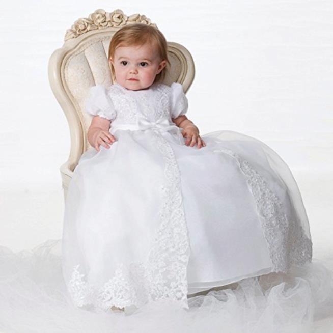 Bambina con tradizionale abito da battesimo