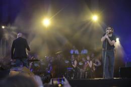 Tommaso Paradiso, in piedi al microfono, davanti all'orchestra