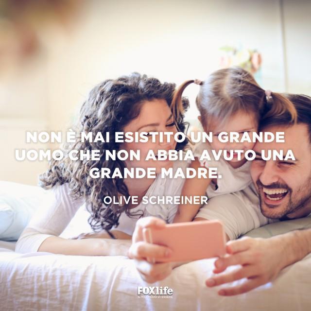 Famiglia a letto con lo smartphone sorride