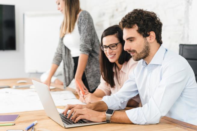 Una donna e un uomo lavorano assiemein un ufficio davanti ad un pc