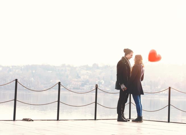 Una giovane coppia su un ponte si tiene per mano guardandosi negli occhi
