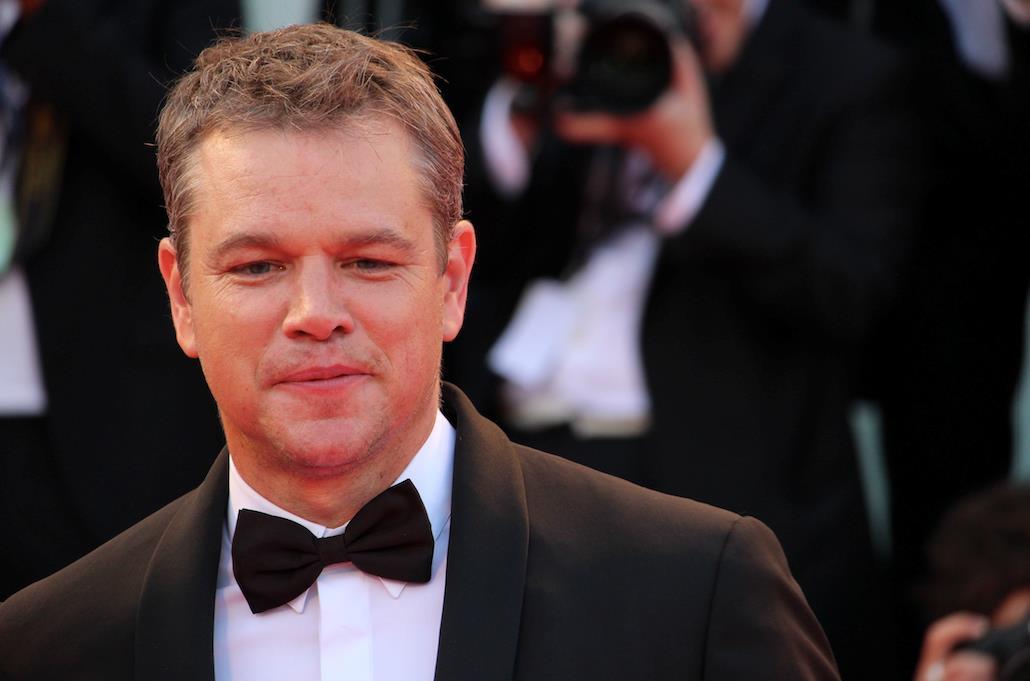 Matt Damon sorride ai fotografi sul red carpet veneziano.