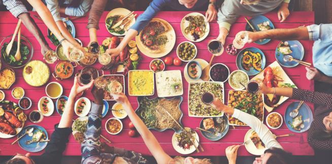 Una tavola ricca di cibo e bevande, molto colorate con tante persone intorno che brindano