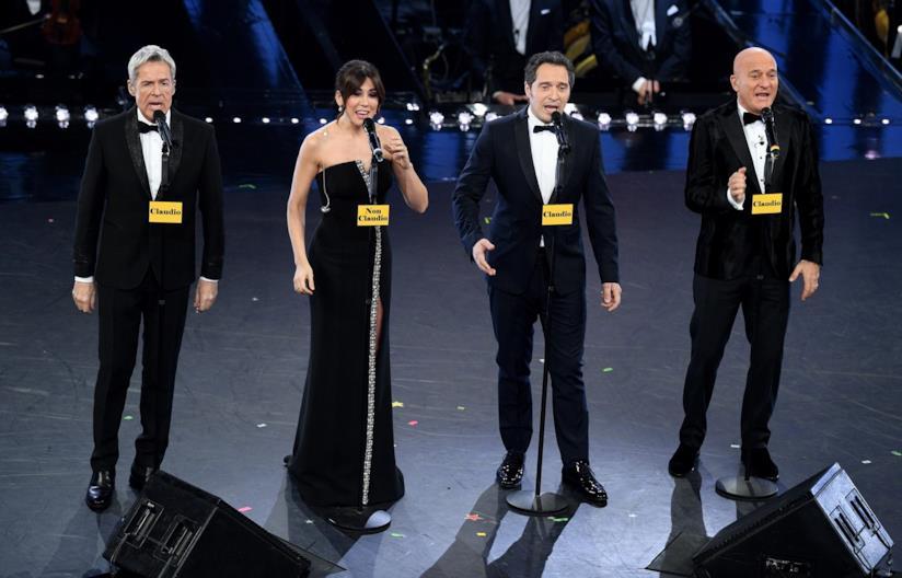 Baglioni, Raffaele, Santamaria e Bisio in nero, di fronte ai microfoni, in piedi sul palco