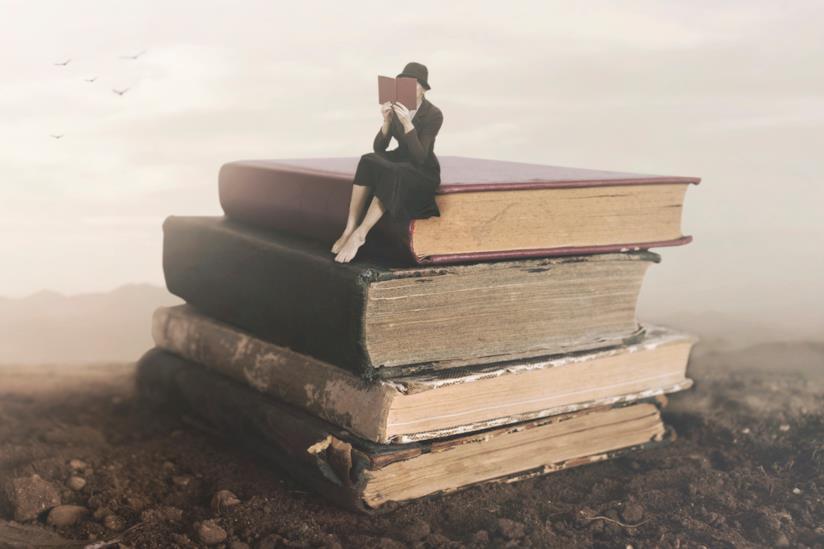 Ragazza seduta sui libri