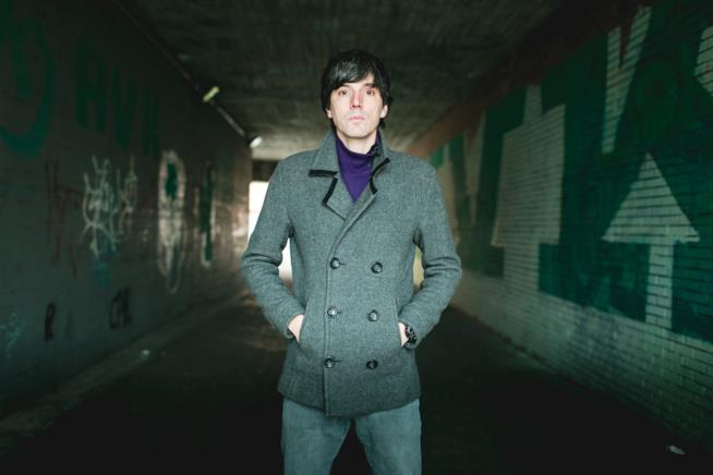 Bugo, in piedi, con una giacca grigia e un paio di jeans in una galleria