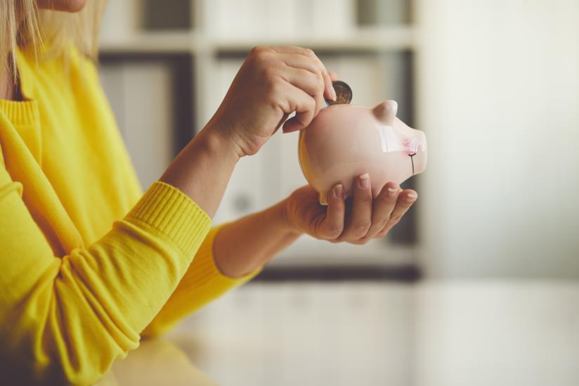 Una donna che mette una moneta nel salvadanaio.