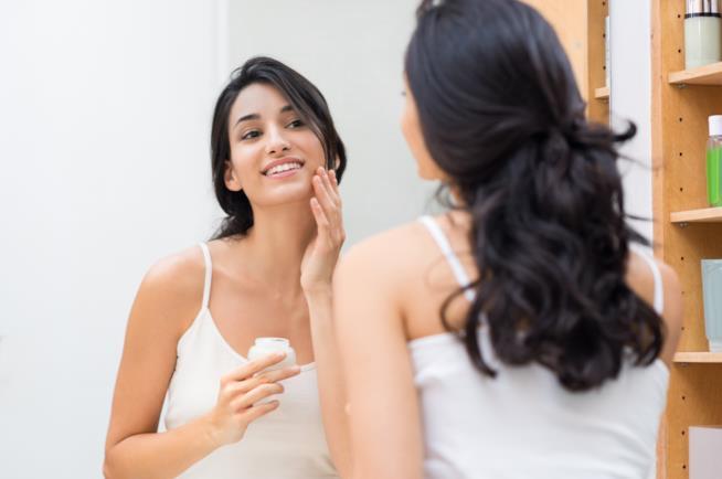 Una donna davanti allo specchio applica sul viso una crema
