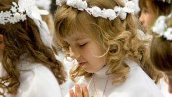 Bambina con l'abito della prima comunione in preghiera