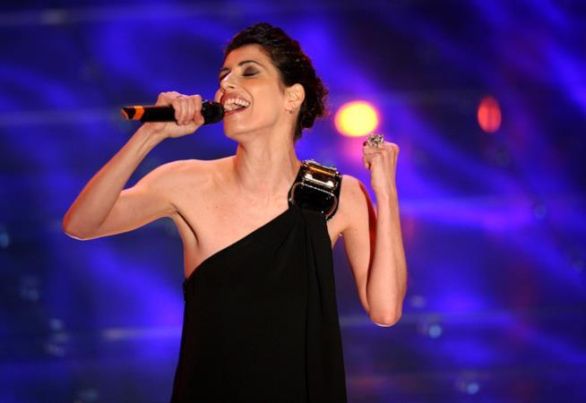 Giorgia con un abito nero, il microfono in mano, su uno sfondo blu