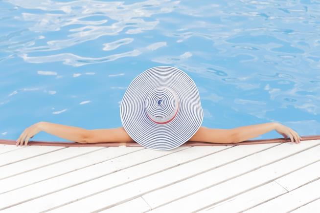 Una donna di spalle mentre è in piscina.