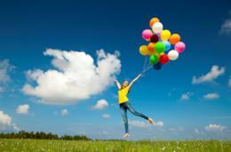 Una donna che salta con palloncini colorati in mano